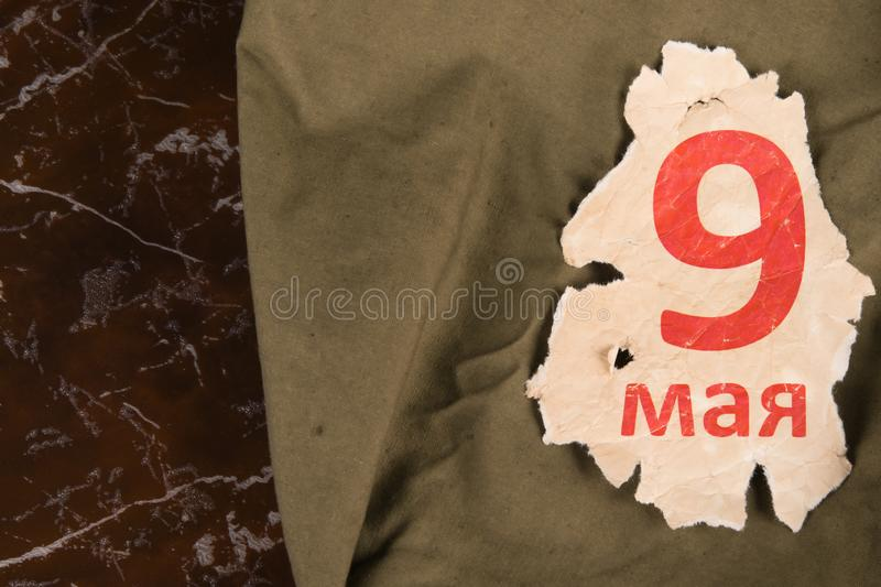 Against the background of a marble monument, a canvas cloak with a calendar sheet on may 9, on the left there is a place for a. Photo of the immortal regiment royalty free stock photography