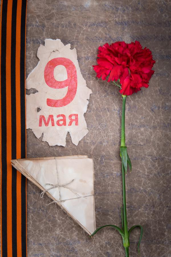 Against the background of old paper, red carnation, St. George ribbon, envelopes and a calendar sheet with the inscription may 9 stock image