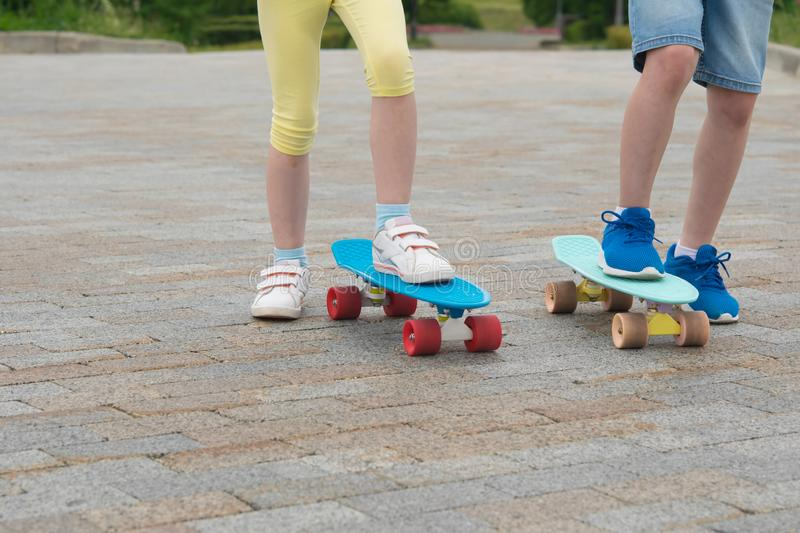 Against the background of stone blocks, close-up of the feet of a boy and a girl on blue skateboards stock photos