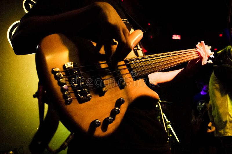 Against bass in close-up on Punk rock show. Photo of a double bass in a punk rock show, dark background and with very well laid out light stock photography