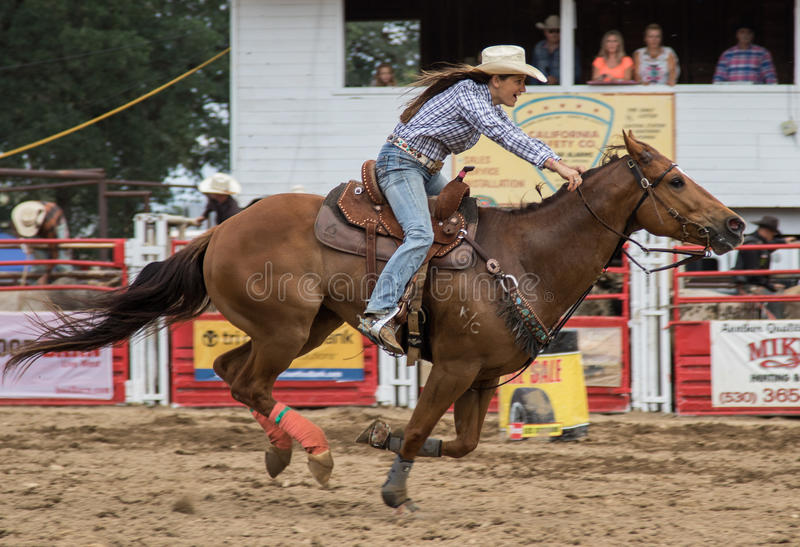 Against the Clock. A cowgirl clears a barrel during a barrel racing event and sprints home. The rodeo in Cottonwood, California is a popular event on Mother's royalty free stock image