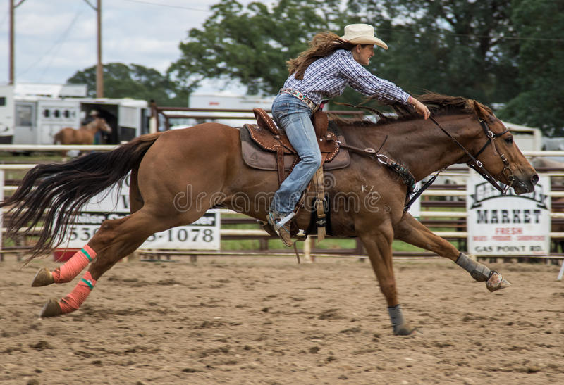 Against the Clock. A cowgirl clears a barrel during a barrel racing event and sprints home. The rodeo in Cottonwood, California is a popular event on Mother's royalty free stock photography
