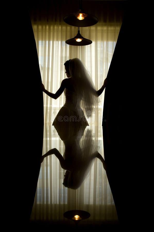 againt新娘反映现出轮廓的视窗 免版税库存照片