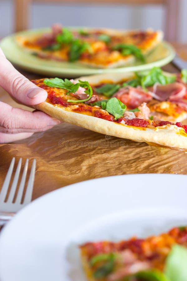 Agarrando uma fatia de pizza imagem de stock