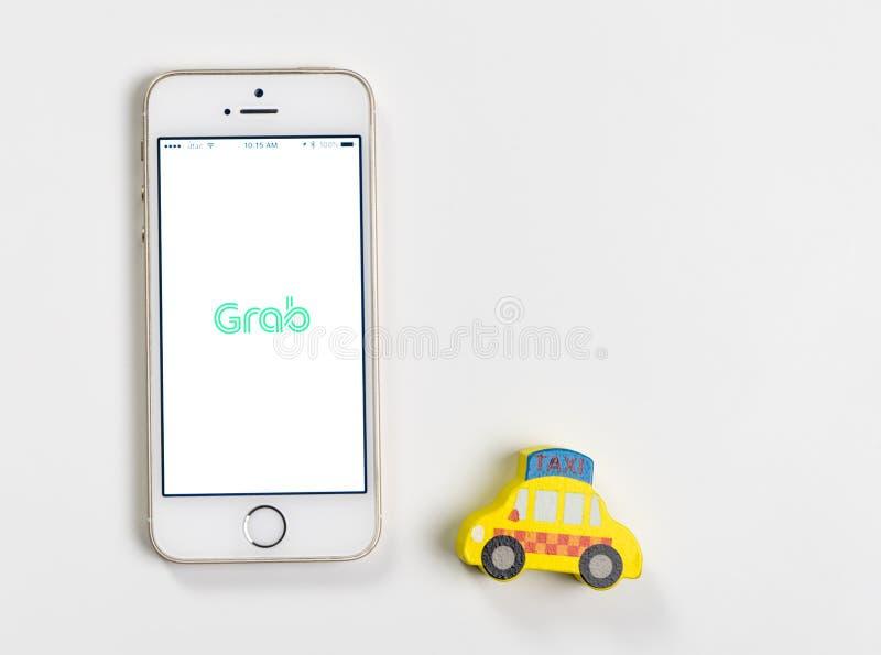 Agarre a aplicação do táxi na tela do iPhone para chamar o táxi fotografia de stock