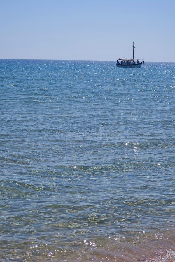 Agathi-stranden i Rhodes och ett fartyg fotografering för bildbyråer