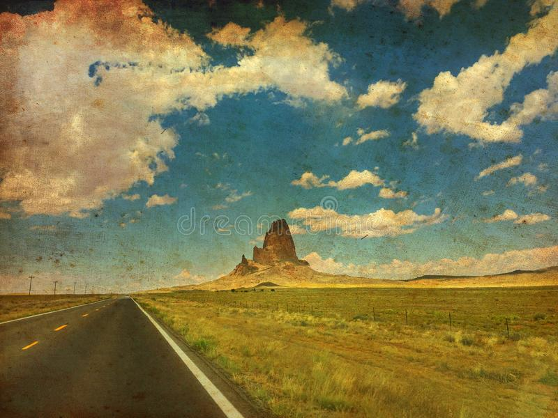 Agathla Peak is a peak south of Monument Valley, Arizona, USA, seen from U.S. Route 163. Made like a vintage canvas painting. The monolith at the highway with stock illustration
