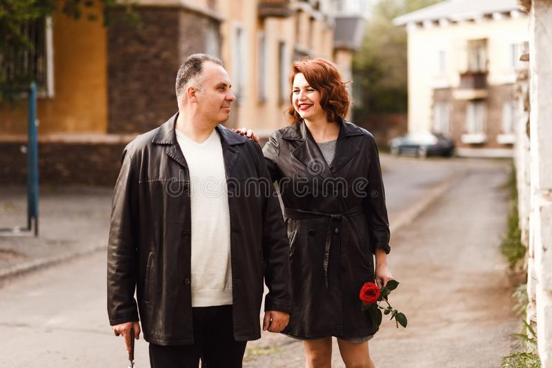 Age couple in leather coats walking through the city streets in the summer. Happy man and woman forty five years old royalty free stock photo