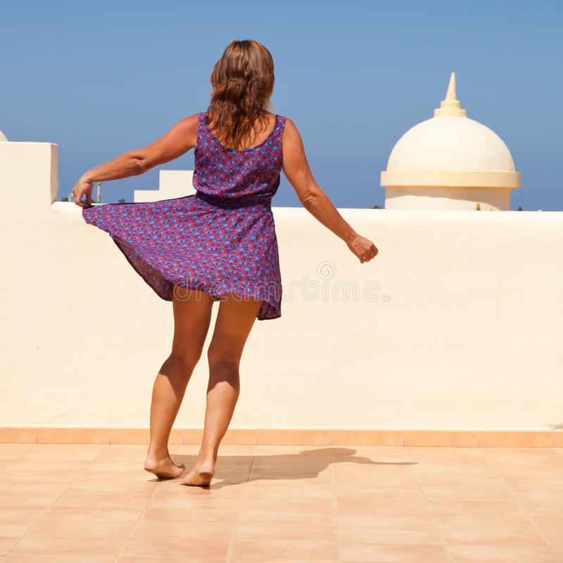 Age doesn't matter. Tanned, fit middle-aged woman dances on the sunroof in short flared dress stock photos