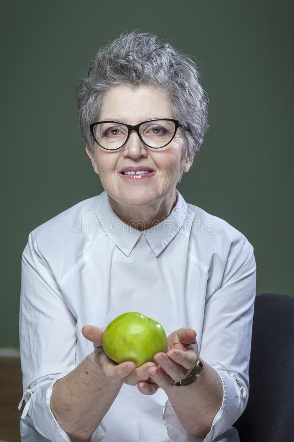 Age, healthy eating, food, diet and people concept - close up of happy smiling senior woman with green apple royalty free stock photo
