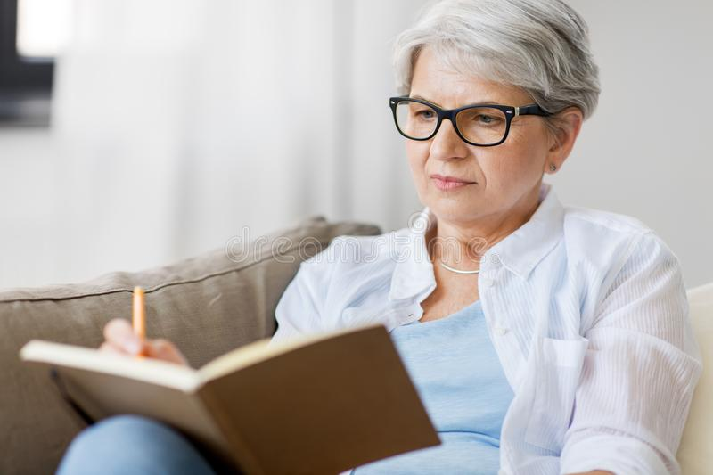 Senior woman writing to notebook or diary at home. Age, leisure and people concept - close up of senior woman in glasses writing to notebook or diary at home royalty free stock photography