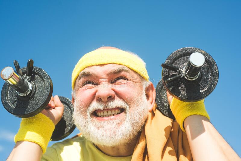 Age is no excuse to slack on your health. Senior man exercising on blue sky. Health club or rehabilitation center for royalty free stock images