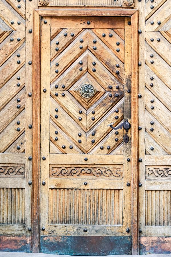 Age-old Brown Wooden Fretwork Door Metal Decor. Closeup age-old light brown wooden fretwork door with metal decoration stock image
