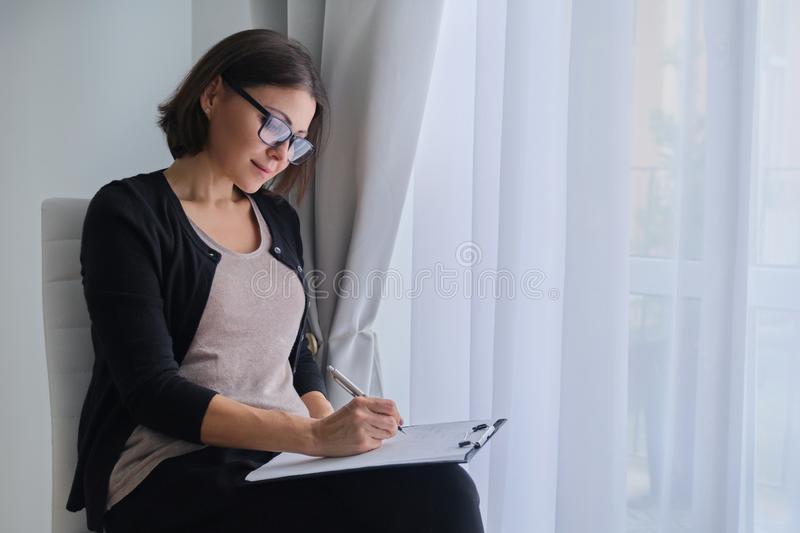 Age woman social worker, psychologist sitting near the window with clipping board stock photos