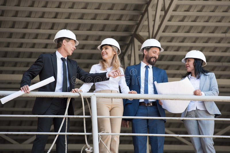 Aged architects in suits talking while standing at construction site. Middle aged architects in suits talking while standing at construction site royalty free stock photography