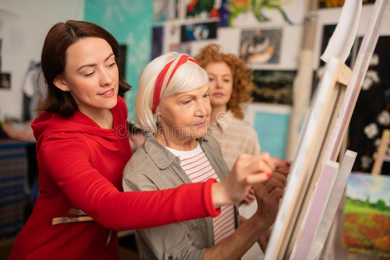 Aged art teacher and her students helping her drawing on canvas stock photos
