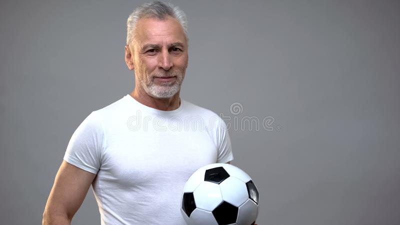 Aged athletic male holding soccer ball, football coach, active lifestyle stock photography