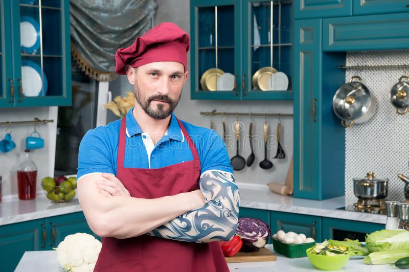 Aged bearded guy with tattooed crossed hands. Guy in red apron stock images