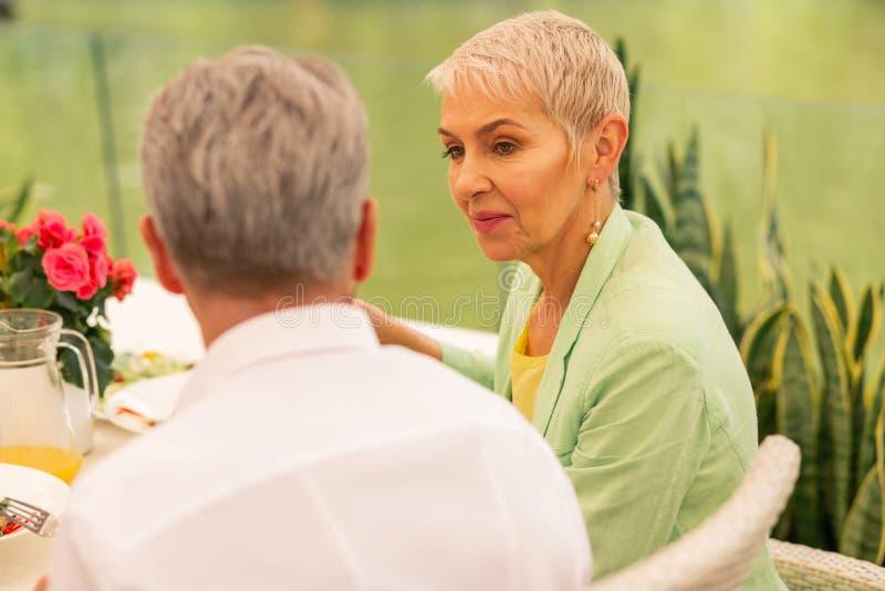 Aged beautiful woman enjoying yummy lunch with husband royalty free stock photos