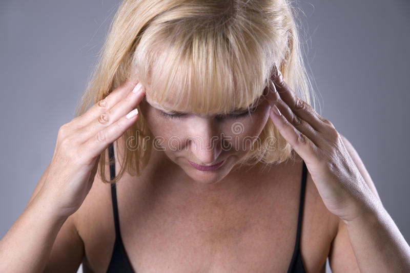 Aged blonde woman with headache, migraine and depression stock image