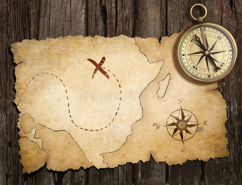 Aged brass antique nautical compass on table with old treasure m. Ap royalty free illustration