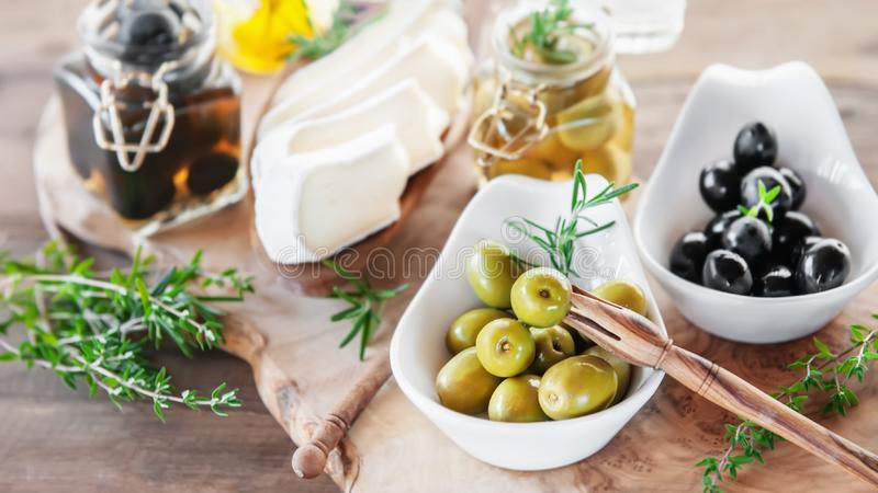 Aged brie cheese on a White dish with olives and Provence herbs wooden table stock image