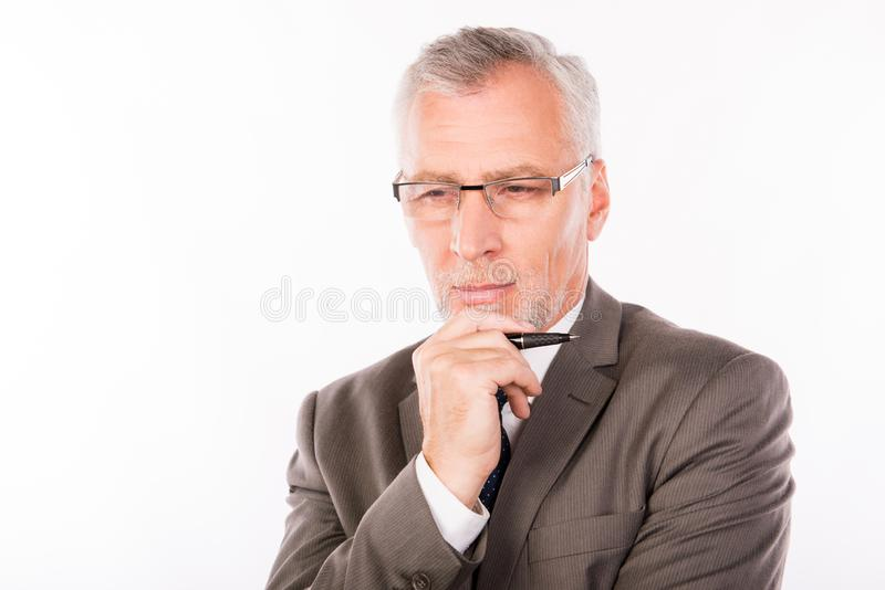 Aged businessman in an elegant suit with glasses holding a pen royalty free stock photos