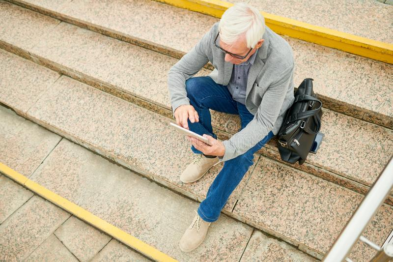 Aged businessman with tablet on stairs stock photos