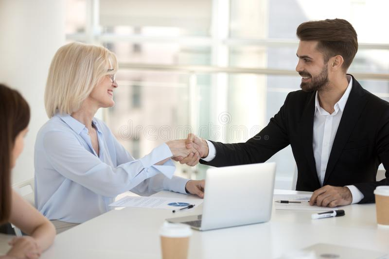 Aged businesswoman shaking hands with client sitting together in boardroom royalty free stock photography