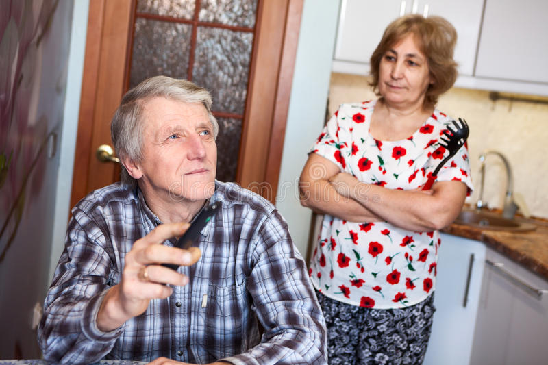 Aged Caucasian husband watching tv with remote control while his anger wife standing behind royalty free stock photography