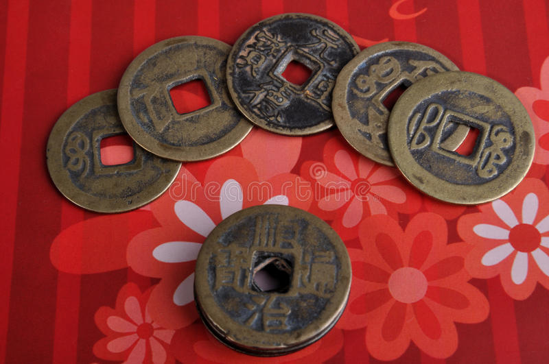 Aged Chinese copper coin. S put on red flower background, means rich and lucky and concept for holiday royalty free stock photography