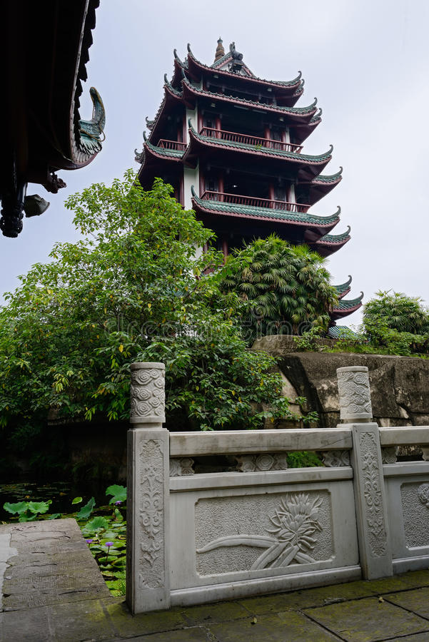 Aged Chinese tower and balustrade by lotus pond in summer royalty free stock photo
