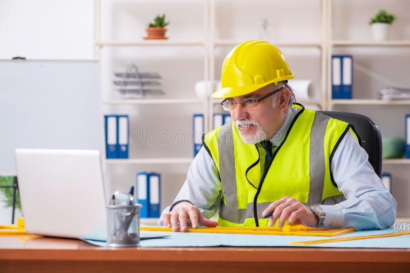 The aged construction engineer working in the office royalty free stock photography