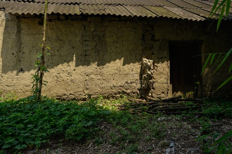Aged cottage with asbestos shingles in sunny summer afternoon stock images