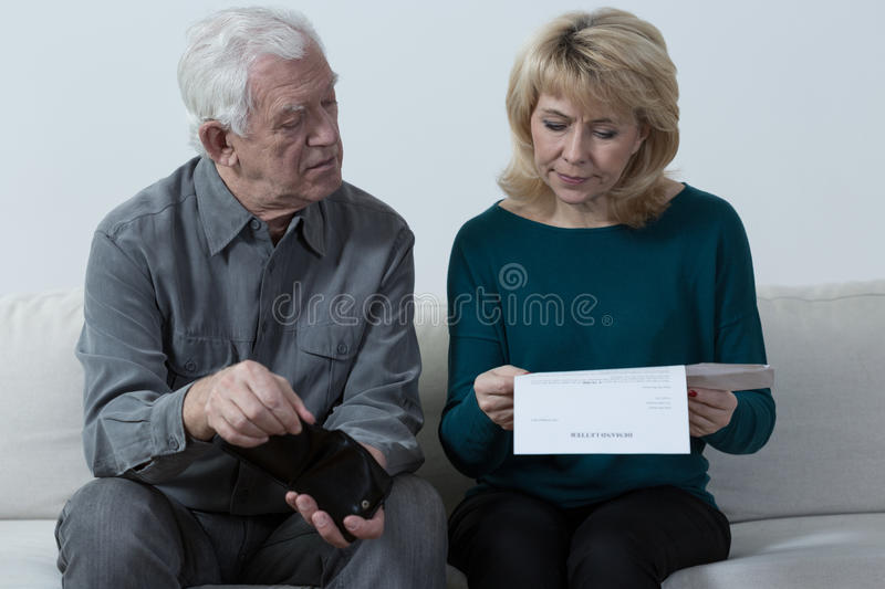 Aged couple analyzing unpaid bills royalty free stock images