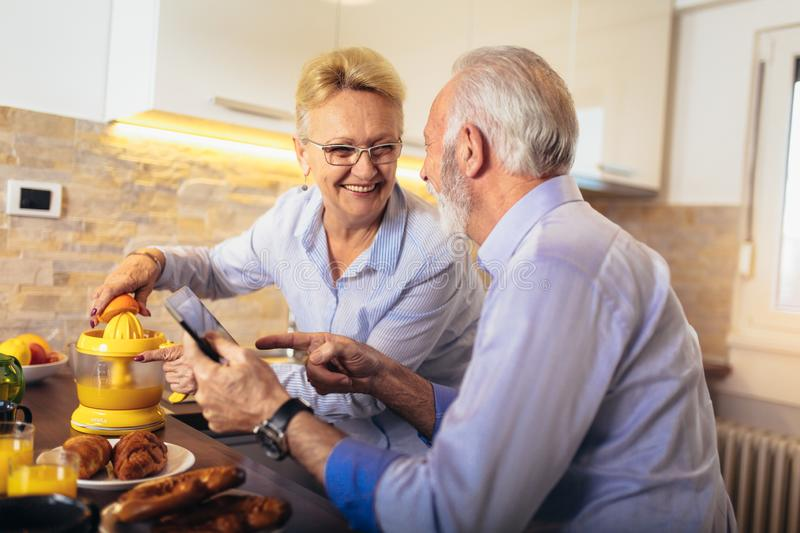 Senior couple busy look at digital tablet while having delicious breakfast at home kitchen royalty free stock photo