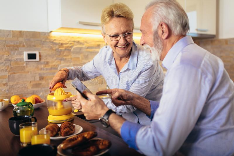 Couple busy look at digital tablet while having delicious breakfast at home kitchen royalty free stock images