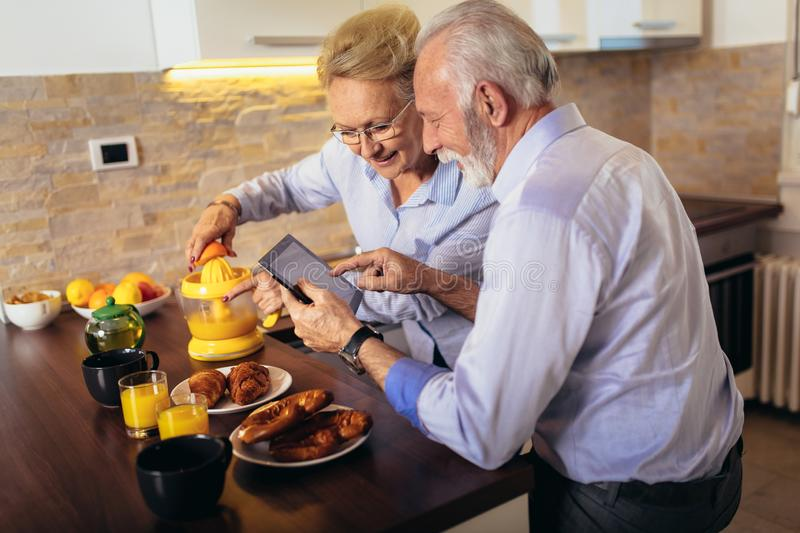 Senior couple busy look at digital tablet while having delicious breakfast at home kitchen stock photos