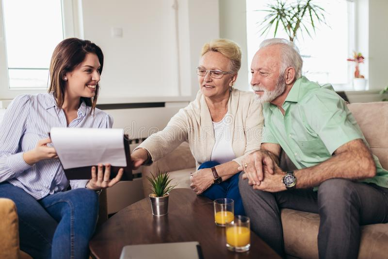 Aged couple consulting with insurance agent. Positive aged couple consulting with insurance agent stock image