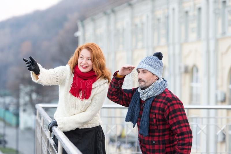 Aged couple looking for friends on other side of bridge. Guy looking in far with hand near of head. Rouge women smile and show to stock image