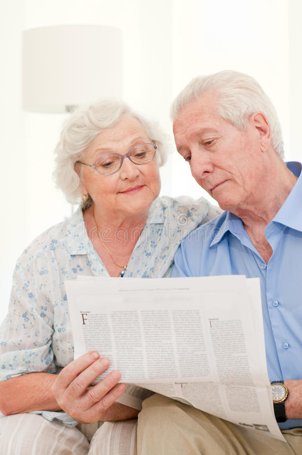 Aged couple reading news