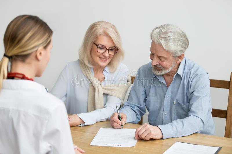 Aged couple signing contract making investment at meeting with a. Aged couple signing contract making investment at meeting with financial advisor, happy senior stock image