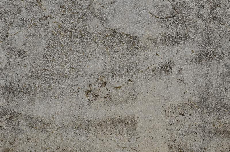 Aged cracked surface of the artificial stone material. Weathered cracked surface of artificial stone made of mixture of mortar and small white marble pieces royalty free stock photos