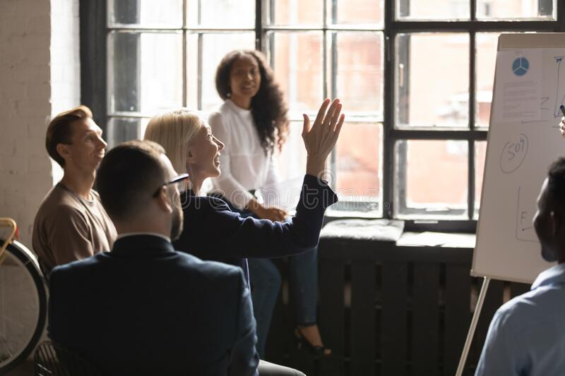Aged curious woman raised hand ask question at corporate seminar stock photos