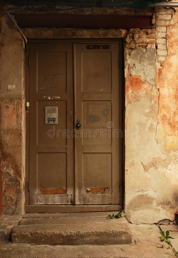 Aged dark wooden door in weathered dirty brick wall stock photo