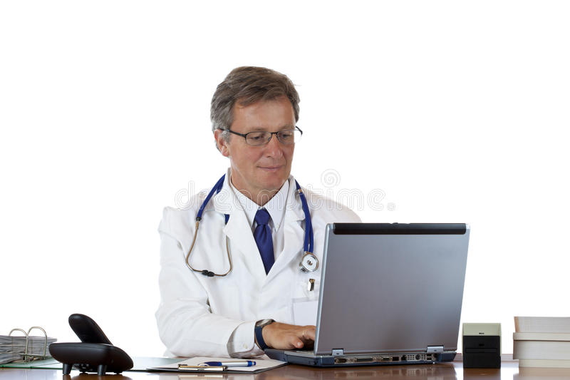 Aged doctor types medical history in laptop royalty free stock photography
