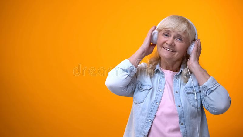 Aged female listening music in headphones, leisure time and entertainment stock image