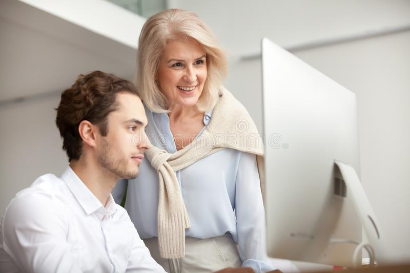 Smiling aged female mentor looking at computer screen helping in stock photo
