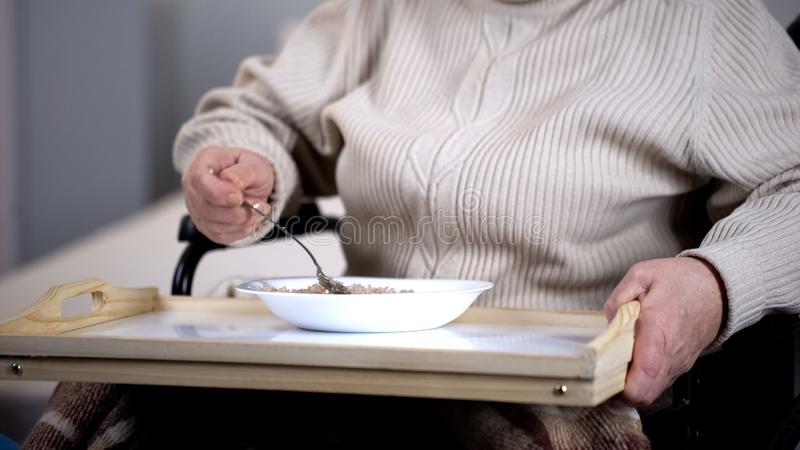 Aged female patient eating porridge, medical care in hospital, nursing home stock photography