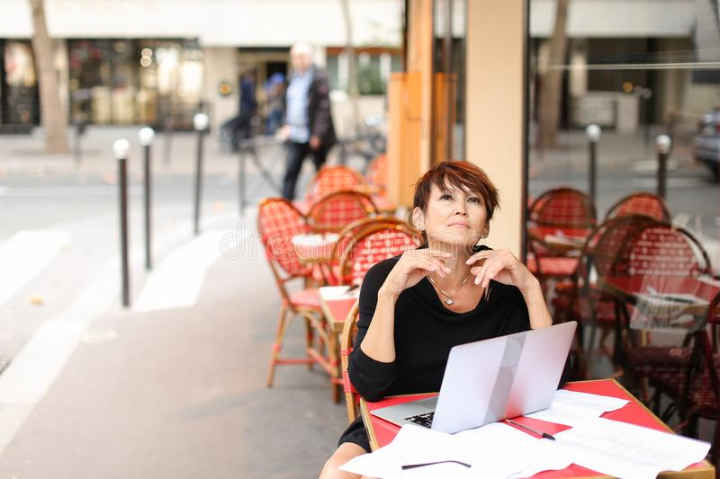 aged female screenwriter working with scenario in laptop. stock photo